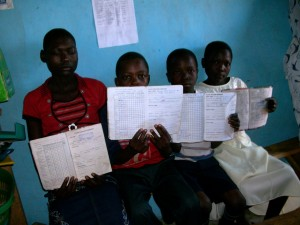 Some of the kids displaying their examination report cards,during their meeting in WEFOCO OFFICE